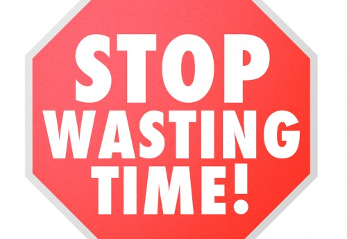 Stop Wasting Time words on a red road warning sign to help you b